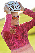 Young  woman puts on her bicycle helmet, Muensing, bavaria, germany