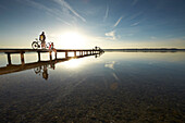 Young  woman and young man with bicycles on a jetty, Muensing, bavaria, germany