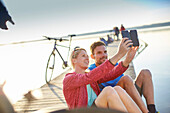 Young  woman and young man with bicycles on a jetty taking a selfie, Lake Starnberg, bavaria, germany