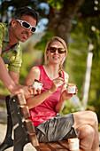 junge Frau und junger Mann, Paar, Pause  auf Fahrradtour, Eis essen, Kochel, Bayern, Deutschland