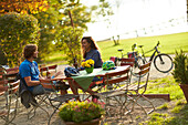 Young  woman and young man on bicycletour sitting in beergarden, Muensing, Lake Starnberg;  bavaria, germany