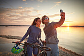 Young  woman on touring bike, young man on touring eBike on tour,taking selfie on  lakeshore, Muensing, bavaria, germany