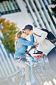 Young  woman kissing young man on eBikes downtown, Munich, bavaria, germany