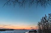 Winter landscape Footbridge on frozen lake in Germany at the blue hour