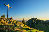Woman hiking sitting at summit of Feichteck, Hochries in background, Feichteck, Chiemgau Alps, Upper Bavaria, Bavaria, Germany