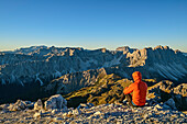 Man hiking sitting at Peitlerkofel and looking towards Dolomites with Marmolada, Sella Group, Langkofel and Geisler Range, from Peitlerkofel, Dolomites, UNESCO World Heritage Site Dolomites, South Tyrol, Italy