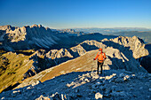 Man hiking ascending towards Peitlerkofel, Geisler Range in background, Peitlerkofel, Dolomites, UNESCO World Heritage Site Dolomites, South Tyrol, Italy