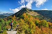 Woman hiking looking towards Schmittenstein, from Schlenken, Salzkammergut, Salzburg, Austria