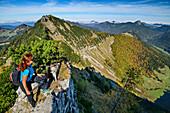 Woman hiking looking over cliff, Regenspitz in background, from Gruberhorn, Salzkammergut, Salzburg, Austria