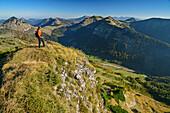 Woman hiking looking towards the valley, Salzkammergut Mountains in background, from Hochwieskopf, Salzkammergut, Salzburg, Austria