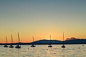 Sailing boats at lake Chiemsee at dawn, Chiemgau alps in background, lake Chiemsee, Chiemgau, Upper Bavaria, Bavaria, Germany