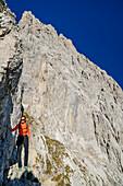 Frau beim Wandern steigt durch steile Felsen zur Lamsenspitze auf, Lamsenspitze, Naturpark Karwendel, Karwendel, Tirol, Österreich