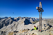 Woman hiking sitting at summit of Lamsenspitze, Lamsenspitze, Natural Park Karwendel, Karwendel range, Tyrol, Austria