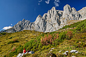 Woman hiking sitting on rock and looking towards rock walls of Kaiser, Wilder Kaiser, Kaiser range, Tyrol, Austria