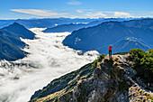 Woman hiking ascending towards Seebergspitze, mood of fog above lake Achensee, Rofan and Karwendel in background, Seebergspitze, Karwendel range, Tyrol, Austria