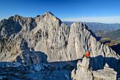 Man sitting on rock spire and looking towards rock walls of Vordere and Hintere Karlspitze, from Hintere Goinger Halt, Wilder Kaiser, Kaiser range, Tyrol, Austria