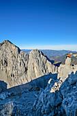 Man sitting on rock spire and looking towards rock wall of Hintere Karlspitze, from Hintere Goinger Halt, Wilder Kaiser, Kaiser range, Tyrol, Austria