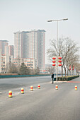 chinese man standing at uncrowded street looking at mobile phone, China National Convention Centre with heavy air pollution, Beijing, China, Asia