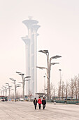 Chineses men (some with air mask) walk through park, Olympic Tower wrapped in heavy air pollution at background, Olympic Green, Beijing, China, Asia