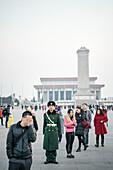 Wachmann steht vor Monument of the People's Heroes und dem Mao Mausoleum umgeben von Besuchern still da, Platz des Himmlischen Friedens, Peking, China, Asien