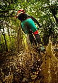 Mountainbikerin fährt durch ein tiefes Schlammloch, spritzender Dreck, Schlamm, Dynamik, Finale Ligure, Italien