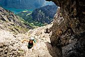 Junge Frau mit Kletterausrüstung steigt in der Watzmann Ostwand auf dem Berchtesgadner Weg auf, Tiefblick auf den Königsee, St. Bartholomä, Berchtesgaden, Bayern, Deutschland