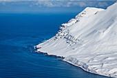 Verschneite Hänge enden im Meer, Tröllaskagi, Island, Skandinavien