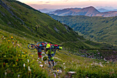 Two mountainbikers carry their bikes on the back, after sunset, green grassy mountain slope, Kirchberg, Tyrol, Austria