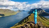 Junge Frau blickt mit dem Fernglas von einem Berg über das Meer und die Fjordlandschaft bei blauem Himmel, Klaksvík, Faröer Inseln