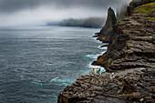 Zwei Mountainbiker stehen an einer Felsklippe am Atlantischen Ozenan, Faröer Inseln