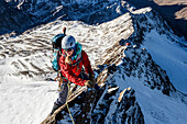 Young female mountaineer climbs on a ridge in the winter, Piz Tresero, Valfurva, Lombardia, South Tyrol, Italy