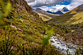 Junge Frau fährt mit dem Mountainbike neben einem Gebirgsfluss, Wokenstimmung, Val Forni, Ortler Gebirge, Königspitze, Valfurva, Lombardei, Italien