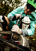 Young woman filling up her mountainbike tyre, Bormio, Lombardia, South Tyrol, Italy