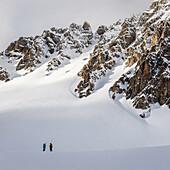 Zwei Skitourengeher begutachten einen felsdurchsetzten, unverspurten Hang, Tuoi Hütte, Scoul, Silvretta, Schweiz
