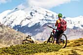 Junge Frau auf dem Mountainbike blickt mit verschränkten Armen auf die Berge des Ortler Gebirges, Bormio, Sondrino, Lombardei, Süditirol, Italien;