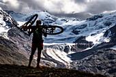Junge Frau mit Mountainbike auf dem Rücken als Silhouette vor Gletscher, Ortlergebirge, Pizzini Hütte, Val Forni, Lombardei, Italien