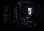 Junge Frau schiebt ihr Mountainbike durch einen Bunker aus dem Ersten Weltkrieg, Silhouette am Ende des Tunnels, Monte delle Scale, Stilfser Joch, Lombardei, Italien