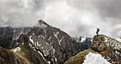 Junge Frau blickt auf die Bergkulisse des südlichen Karwendels, Tirol, Österreich