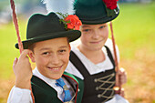 Kids in  Traditional bavarian clothes on a swing, Ammerland, bavaria, Germany