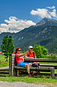Man and woman sitting on bench and having a break, Lechtal Alps in background, Weissenbach, Lechweg, valley of Lech, Tyrol, Austria