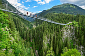 Several persons walking on suspension bridge, Holzgau, Lechweg, valley of Lech, Tyrol, Austria