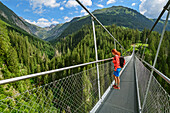 Woman standing on suspension bridge and looking down, Holzgau, Lechweg, valley of Lech, Tyrol, Austria