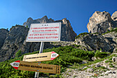 Signpost and info board of fixed-rope route with rock spires of Sella in background, fixed-rope route Pisciadu, Sella range, Dolomites, UNESCO World Heritage Site Dolomites, South Tyrol, Italy