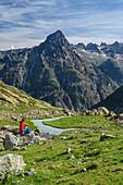 Woman Sitting On rock while hiking and views of Aiguille Du Plat de La Selle, on the Lac Bèches, Ecrins, Ecrins National Park, Dauphiné, Dauphiné, Hautes Alpes, France