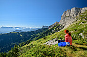 Woman while hiking sits on, paragraph and overlooks the mountain scenery, the Grand Veymont, Vercors, Dauphine, Dauphine, Isère, France