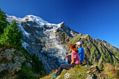 A man and a woman sitting on pointed back and views of Mont Blanc, pyramid, Mont Blanc, Grajische Alps, the Savoy Alps, Savoie, France