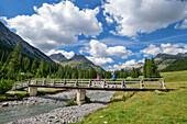 Mann und Frau wandern auf Brücke über den Lech, Lechweg, Lechquellengebirge, Vorarlberg, Österreich