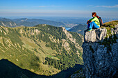 Woman Sitting On rock while hiking(and looks into the depths, Aiplspitze, Mangfall Mountains, the Bavarian Alps, Upper Bavaria, Bavaria, Germany