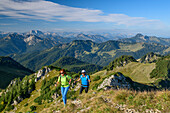 A man and a woman walking on, rising to the Aiplspitze Aiplspitze, Mangfall Mountains, the Bavarian Alps, Upper Bavaria, Bavaria, Germany