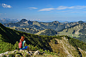 Woman while hiking sits on, paragraph and overlooks Bavarian Alps, Hunter Kamp, Mangfall Mountains, the Bavarian Alps, Upper Bavaria, Bavaria, Germany